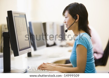 Woman wearing headset in computer room typing and smiling