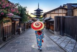 woman wearing japanese traditional kimono with umbrella at Yasaka Pagoda and Sannen Zaka Street in Kyoto, Japan.