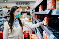 Woman wearing mask buying groceries/supplies in supermarket with sold out products.Food supplies flour shortage.Empty shelves due to novel coronavirus covid-19 outbreak panic buying and hoarding.