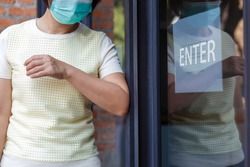 Woman wearing mask opening the door with the elbow for protection  infection COVID-19