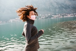 Woman wearing medical mask, Coronavirus pandemic Covid-19. Sport, Active life in quarantine. Outdoor run on athletics track in Corona Outbreak.