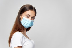woman wearing medical mask looking ahead brunette isolated background