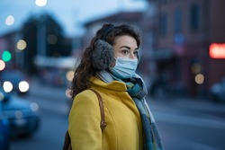 Woman wearing medical protective mask at dusk. Young woman wearing face mask against pollution standing outdoors on winter evening. Girl with earflap in winter city street during coronavirus outbreak.