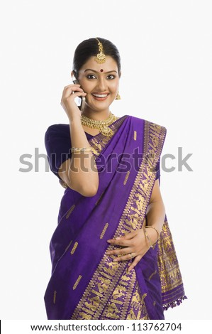 Woman wearing mekhla and talking on a mobile phone