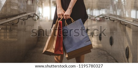 Woman wearing modern suit holding shopping bags, ideas for shopping concept.