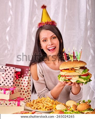Woman wearing party hat eating hamburger at birthday. Shopping bag,