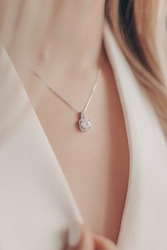 Woman wearing pendant necklace with diamond on close-up