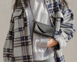 Woman wearing plaid trendy jacket on a gray hoodie with a black leather bag with her hand in her pocket.