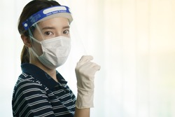 Woman wearing protection medical screen or plastic shield on her face, for corona virus or Covid-19 protection.