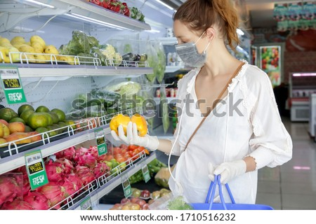 Woman wearing protective mask and latex gloves while grocery shopping in supermarket, Coronavirus contagion fears concept