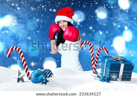 Woman wearing red boxing gloves against christmas scene with gifts and candy canes