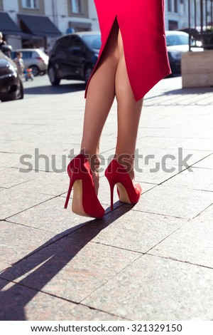 Woman wearing red elegant skirt  and red high heel shoes in old town.Sexy legs in red high heel shoes.Outdoor Romantic photo of woman walking in old town.Woman wearing red high heel shoes.