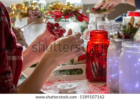 Woman wearing red plaid shirt making Christmas crafts in the kitchen with snow painted jars, pine cones, holly and poinsettias.