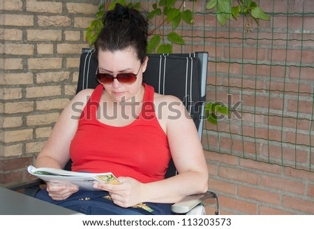 Woman wearing red tank top and sunglasses is reading a magazine