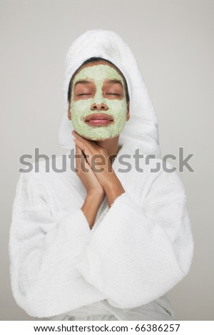Woman wearing robe with beauty mask on face