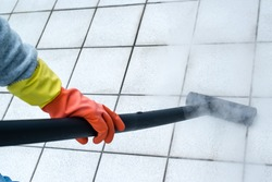 Woman wearing rubber gloves using steam cleaner to brighten up balcony tiles