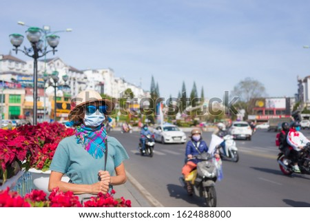 Woman wearing sanitary mask outdoors in Da Lat city centre Vietnam. Medical mask protection against risk of new corona virus covid-19 epidemy in Asia. Anti smog mask traffic pollution.