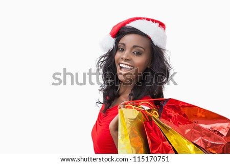 Woman wearing Santa Claus hat while holding bags - stock photo