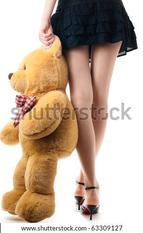 woman wearing skirt and high heels, holding toy bear near her legs, view of the back lower body part, isolated on white background