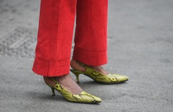 Woman wearing snakeskin shoes and red pants.