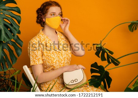 Woman wearing stylish handmade protective face mask, flower print dress, holding bag, posing on orange background. Monochrome outfit. Fashion during quarantine of coronavirus outbreak. Copy space