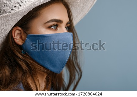 Photo of Woman wearing stylish protective face mask, posing on blue background. Trendy Fashion accessory during quarantine of coronavirus pandemic. Close up studio portrait. Copy, empty space for text