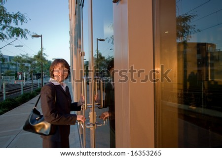 Woman wearing suit smiles at camera while opening door. She has a purse over her shoulder. Horizontally framed photo.