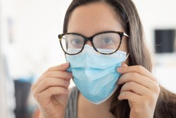 Woman wearing surgical mask due to the pandemic but its cause the fogging of the glasses. Problem of fogging of the glasses due to the wearing of the surgical mask.