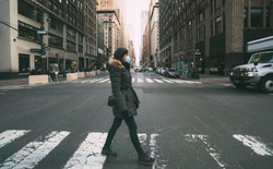 Woman wearing surgical mask going through crosswalk in midtown manhattan.Concept of Coronavirus, COVID-19 and quarantine