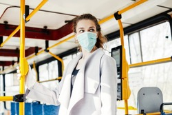 Woman wearing surgical protective mask pushing the button in a public transportation