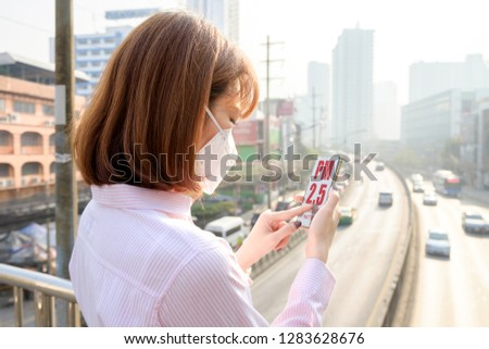 Woman wearing the N95 Respiratory Protection Mask and using smart phone app with PM 2.5 screen.
