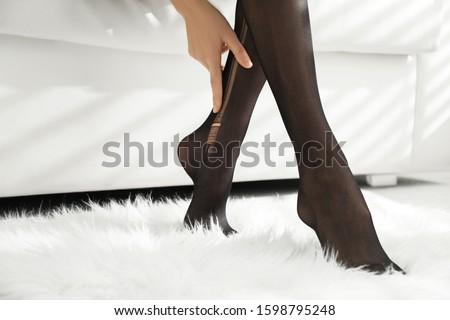 Woman wearing torn tights at home, closeup