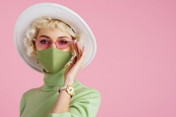 Woman wearing trendy fashion outfit during quarantine of coronavirus outbreak. Model dressed protective stylish handmade face mask, pink sunglasses, white hat, wrist watch, green mint color turtleneck