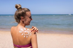 Woman wearing two piece bikini applying suncream with sun drawn on back on the tropical beach.Summer vacations. Beautiful Woman with Sunscreen Solar Cream over ocean background. Sun Tanning.