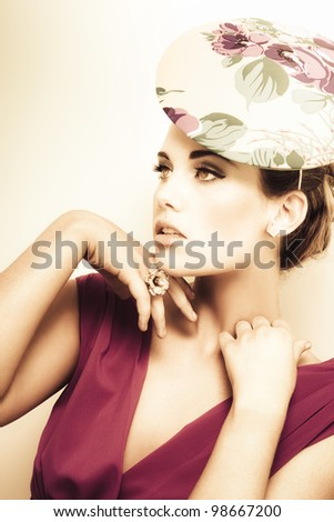 woman wearing v-neck blouse and floral hat, flower ring on her finger, hands touching her neck