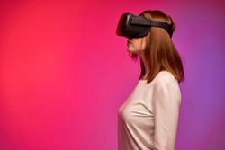 Woman wearing virtual reality device to play video game, looking forward, dressed casually. Portrait of female with short hair engaged in VR. side view. hi-tech concept. Bright vivid background