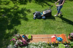 Woman wearing wellington boots mowing grass with lawn mower in the garden, gardening tools concept