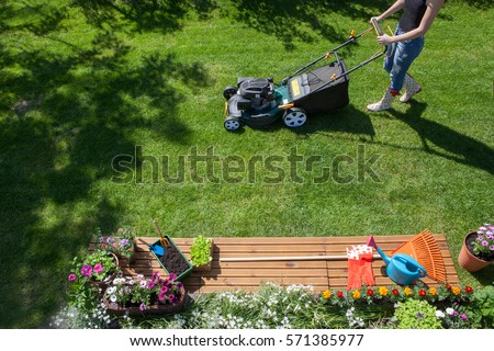 Woman wearing wellington boots mowing grass with lawn mower in the garden, gardening tools concept  #571385977