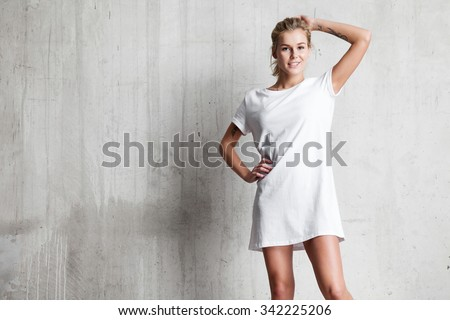 Woman wearing white blank t-shirt  standing on the background of a cement wall Photo stock ©