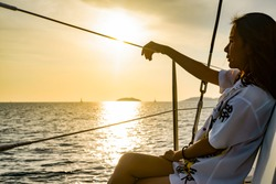 woman wearing white shirt sitting alone in a sailboat with feeling sad lonely missing thinking for something with ocean sea and twilight sky and sunset in the evening. Relax trip on holiday vacation.