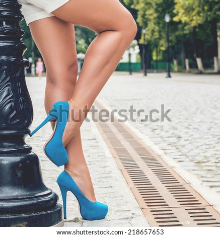 Woman wearing white shorts and blue high heel shoes in old town