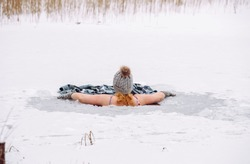 Woman wearing wool hat, mittens gloves and swimsuit, swimming dipping inside homemade ice hole in lake. Healthy winter ice bath concept.