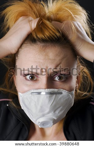 Woman wears a face mask and medical scrubs with a wide-eyed expression of concern or fear