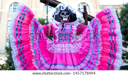 Woman wears sugar skull mask and bright pink Jalisco dress in celebration of Dia de los Muertos / Day of the Dead #1457178494