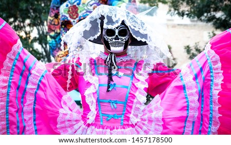 Woman wears sugar skull mask and bright pink Jalisco dress in celebration of Dia de los Muertos / Day of the Dead #1457178500