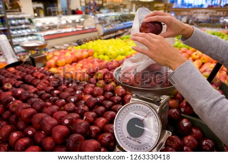 Woman weighing apples in produce section of supermarket