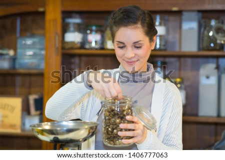 woman weighing fasteners from glass storage jar #1406777063