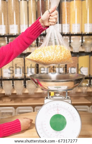 Woman weighing food in bulk section of grocery store