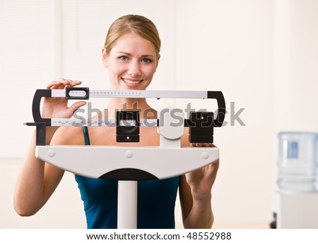 Woman weighing herself on scales in health club