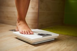 Woman weighing herself on weight scale in bathroom